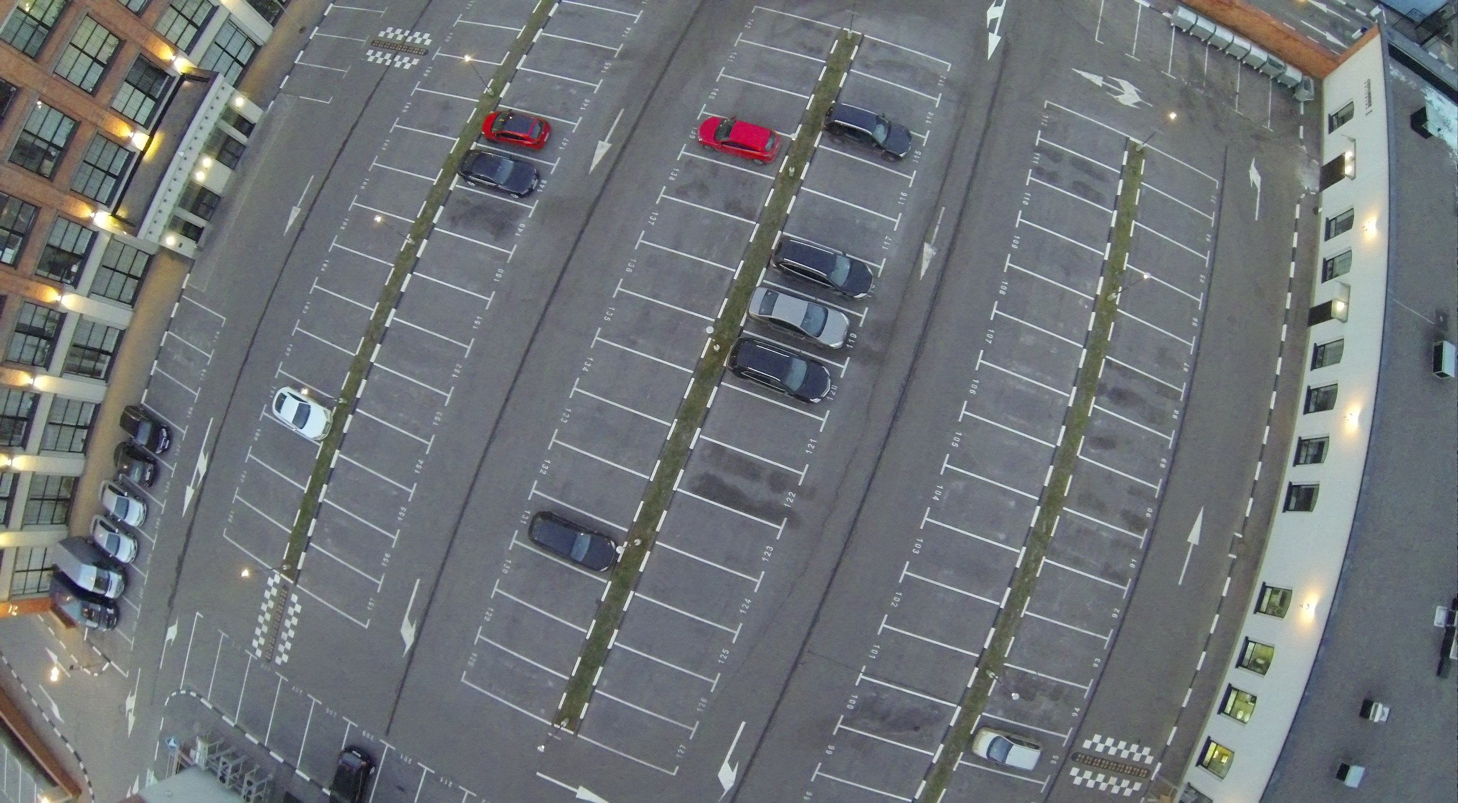 Aerial view of parking lot with few vehicles