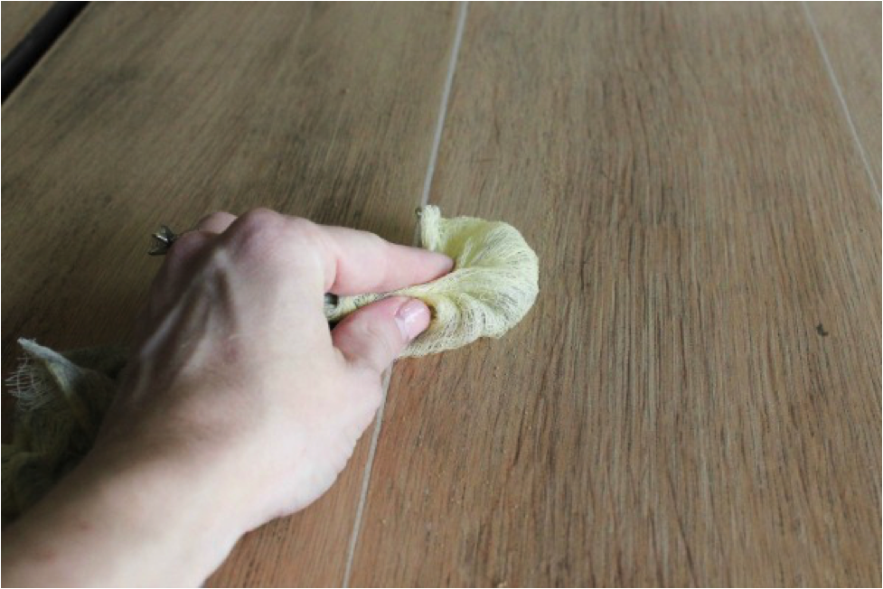 Person staining wood with rag