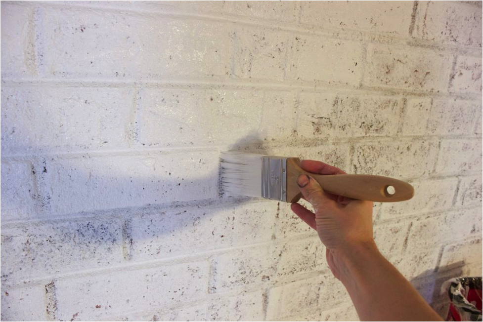 Person painting a brick wall white