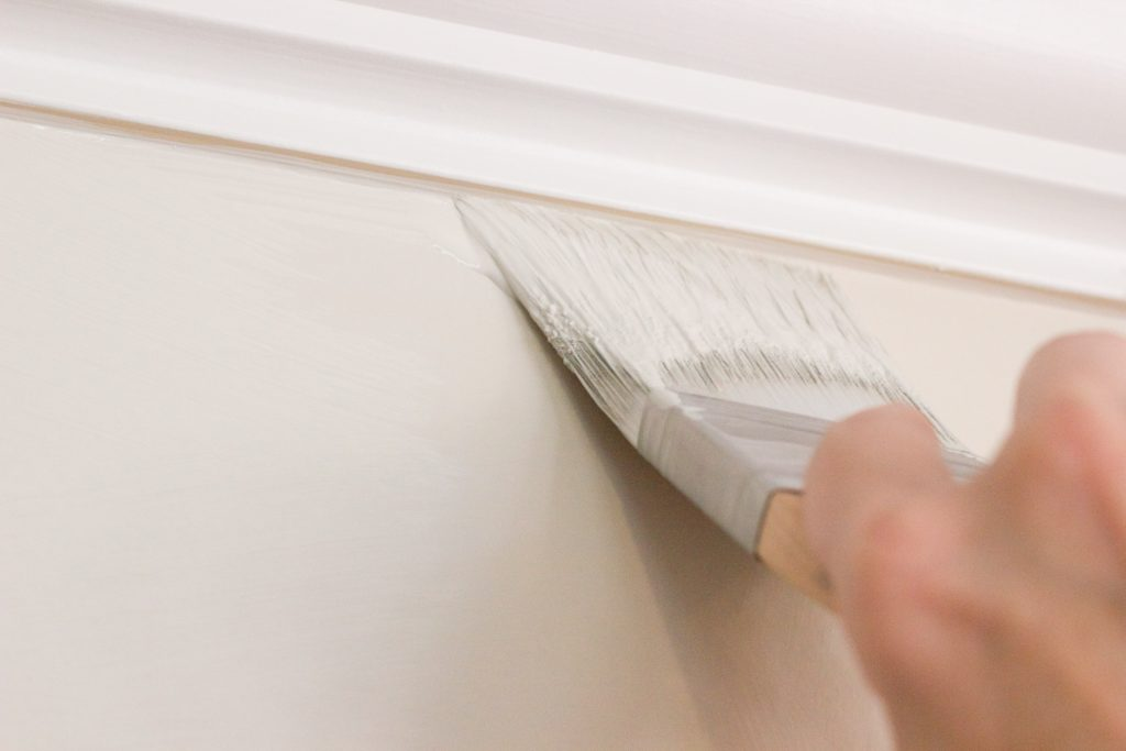 Person with angled paintbrush painting walls white