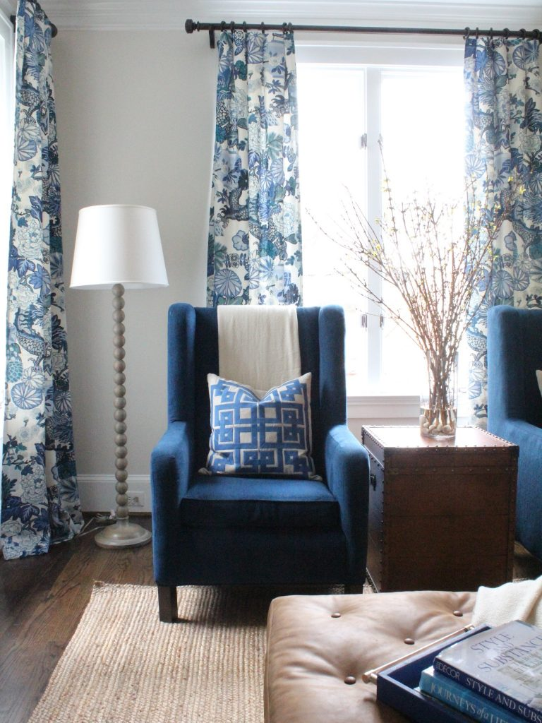 Room with blue chair and faux plant with branches