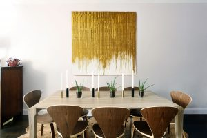 Dining room with tan table, brown chairs and modern gold and white painting