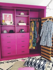 Bright pink dresser and shelves with colorful rug