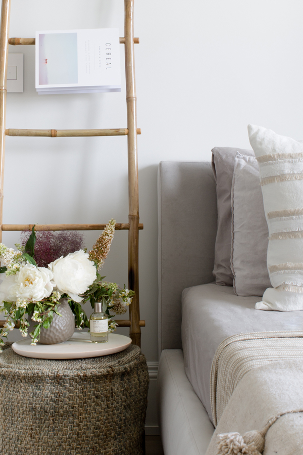 Side table with ladder fixture next to bed
