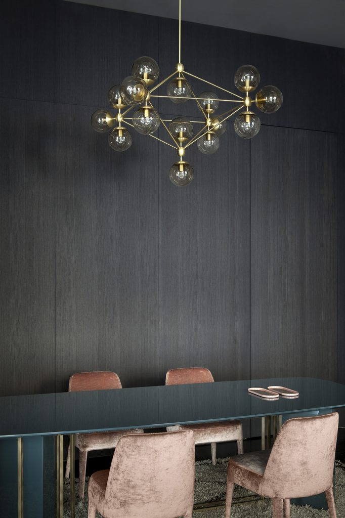 Modern gold light fixture over long dining table