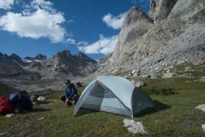 man setting up tent in mountains