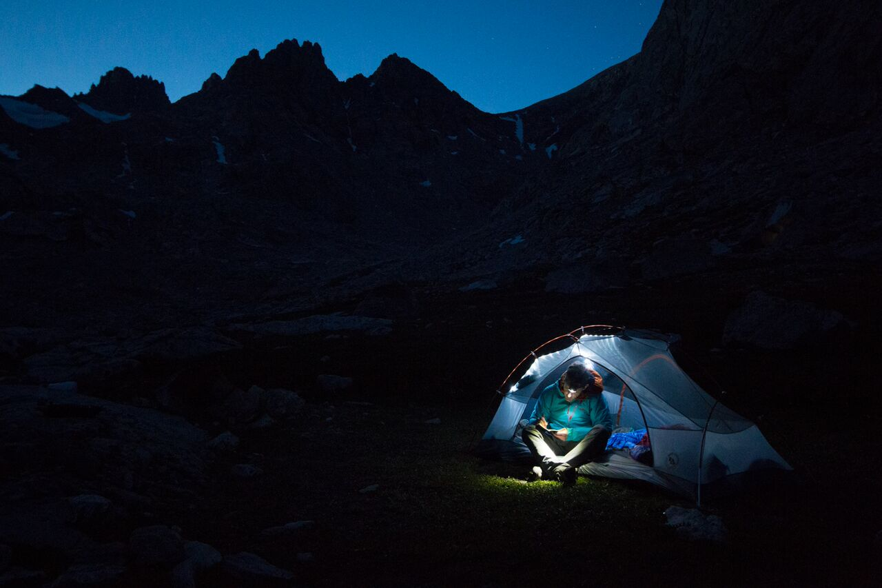 Man sitting in tent at night writing under light
