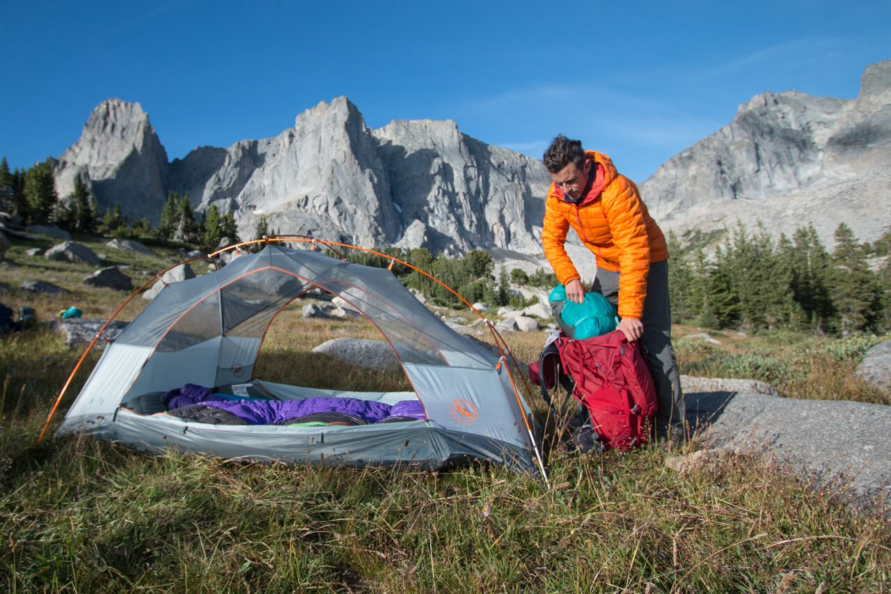 Man packing bag in front of tent in mountainous area