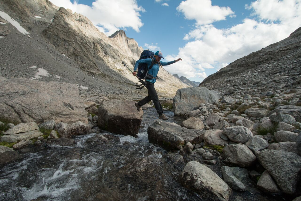 Woman stepping from rock to rock in mountainous area