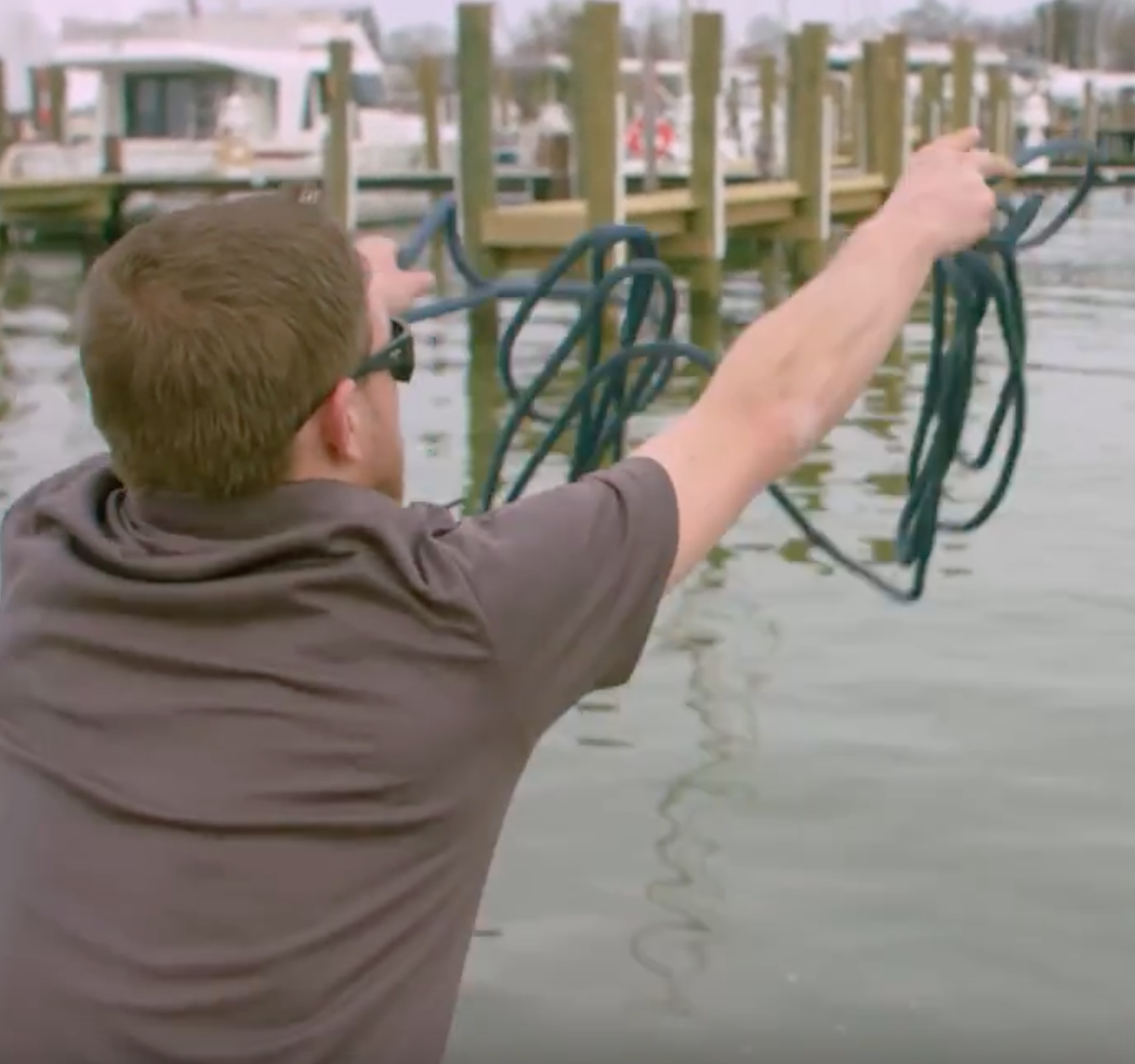 man throwing out rope in lake