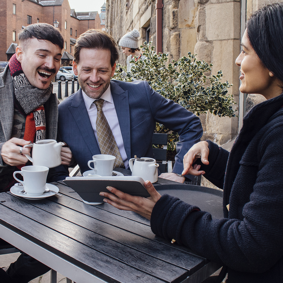 Happy couple are sitting with a financial advisor at a cafe