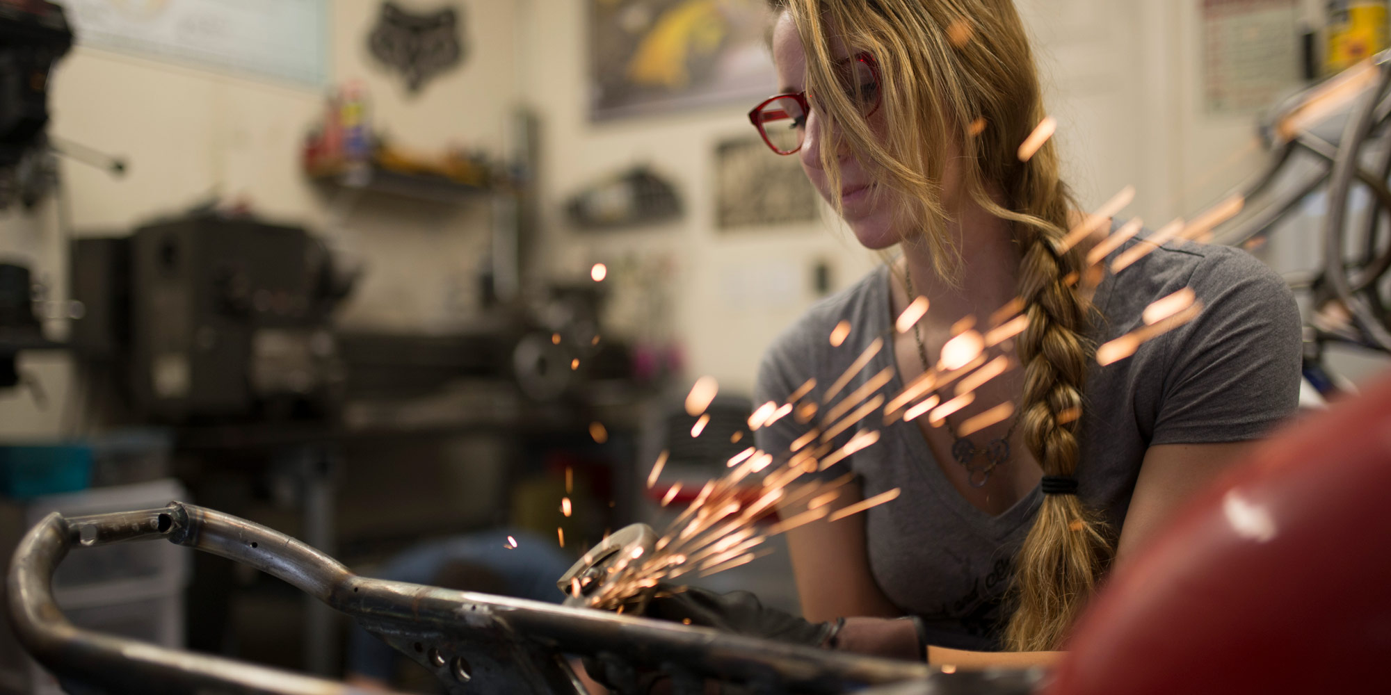 woman working on motorcycle with welding sparks flying