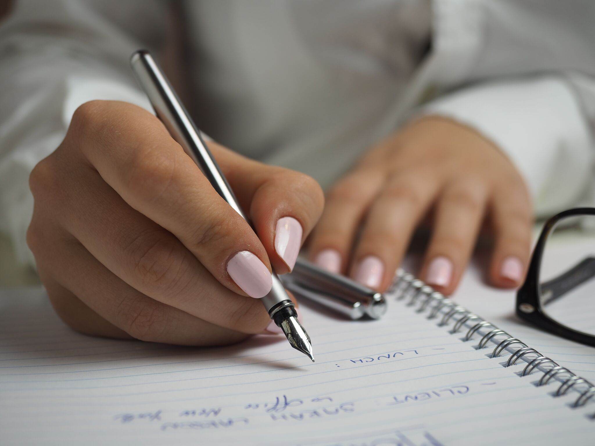 woman writing with pink nail polish