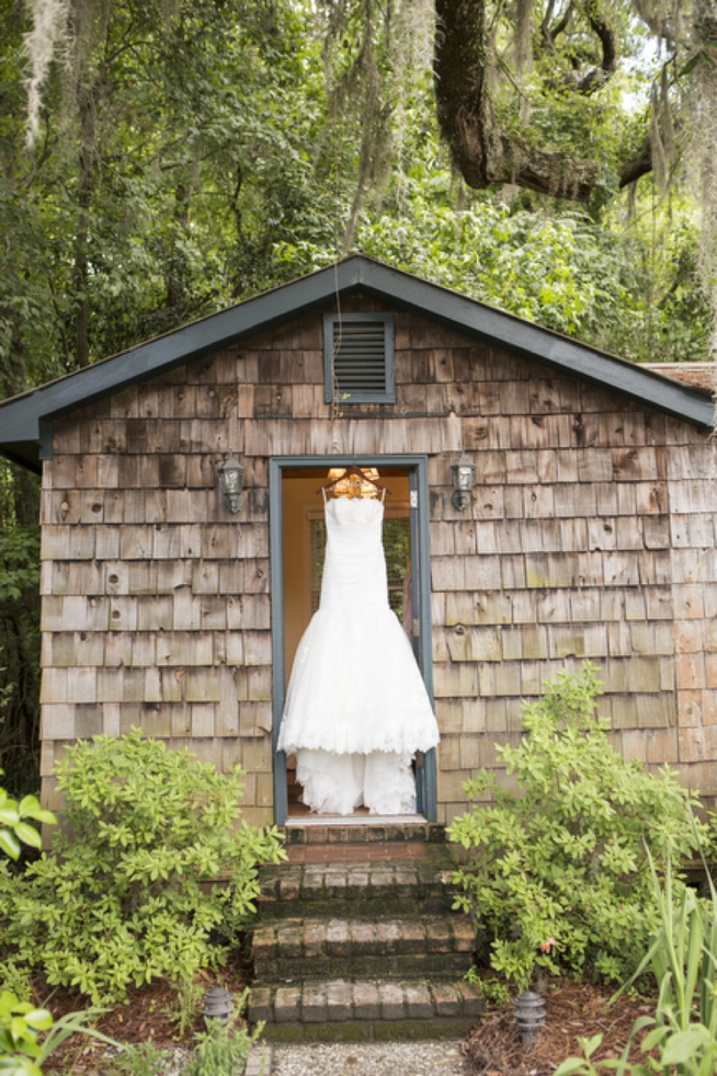 wedding dress hanging from barn door