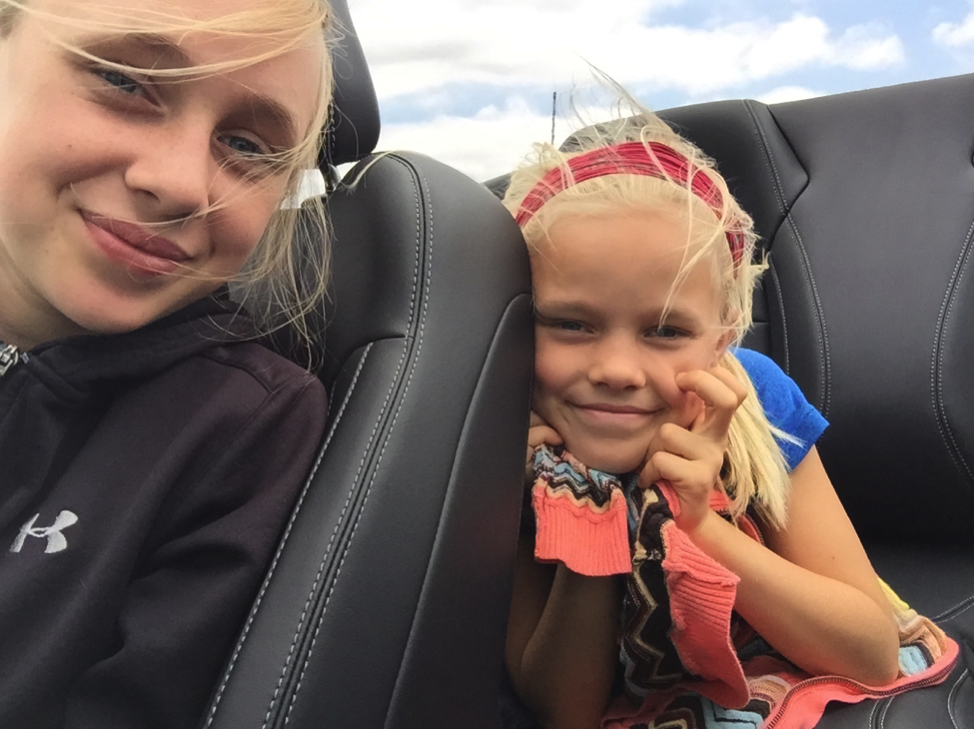 two blond girls in convertible