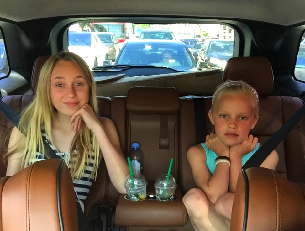 two blond girls in backseat of car
