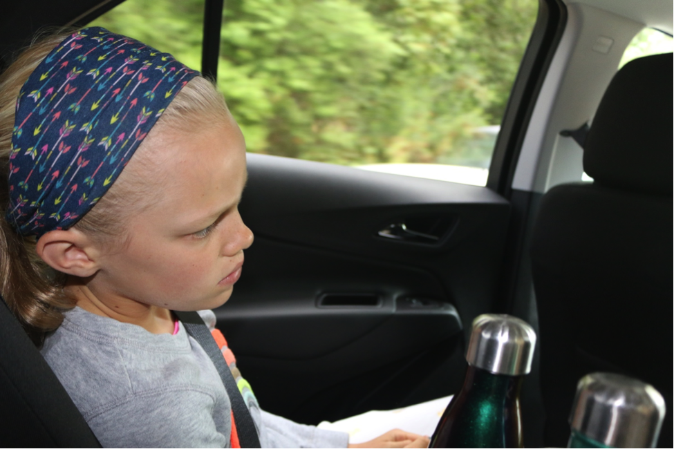 blond girl with headband in backseat of car