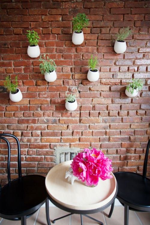 white planters mounted on brick wall