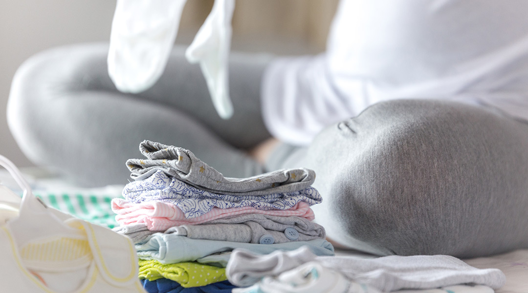 pregnant mother folding baby clothes