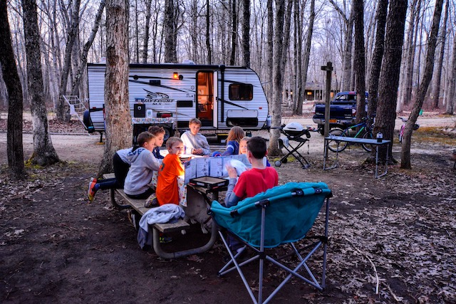 kids sitting around table in front of rv